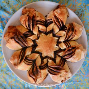 A loaf of mexican chocolate star bread viewed from above. I the center is an 8 pointed star.The golden bread star is surroundd by about 1 inch of chocolate filling. A brange of bread goes out from each point of the star. The left side of each brange shows 4 layers of bread with chocolate and cinnamon in between. The right side of each branch also has 4 layers. The top left side of each branch is tucked under the right side. The pattern looks like vees going from each point of the star.