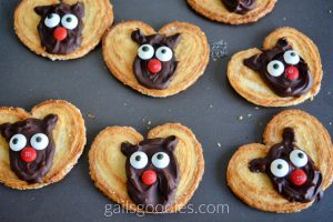 Six moose palmiers are scattered in two rows on a baking tray. The middle of each golden heart-shaped palmier is decorated with a semi-sweet chocolate moose face. Semi-sweet chocolate is swirled into an oval with two small ears. Candy eyes and a red M&M nose give the face features.