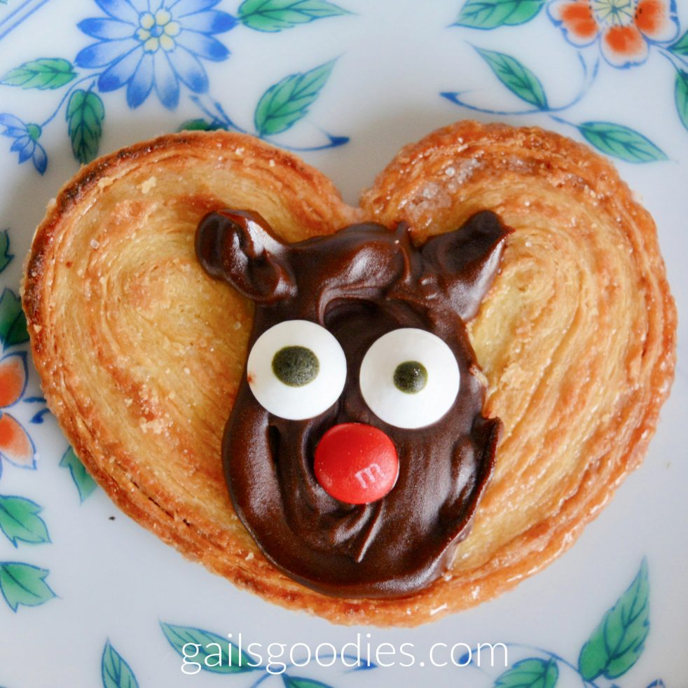 A single moose palmier sits on a white plate with blue and orange flowers. The middle of the golden heart-shaped palmier is decorated with a semi-sweet chocolate moose face. Semi-sweet chocolate is swirled into an oval with two small ears. Candy eyes and a red M&M nose give the face features.