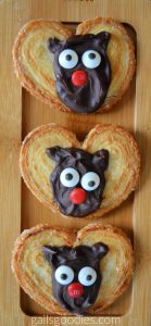 Three moose palmiers are arranged vertically on a wooden tray. The middle of each golden heart-shaped palmier is decorated with a semi-sweet chocolate moose face. Semi-sweet chocolate is swirled into an oval with two small ears. Candy eyes and a red M&M nose give the face features.