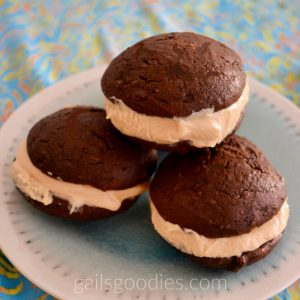 Four peanut butter whoopie pies are stacked in a pyramid on a light teal plate. Only three whoopie pies are visible. Two on the bottom and one on the top. A thick layer of creamy peanut butter filling is sandwiched between two large, moist chocolate cake cookies.