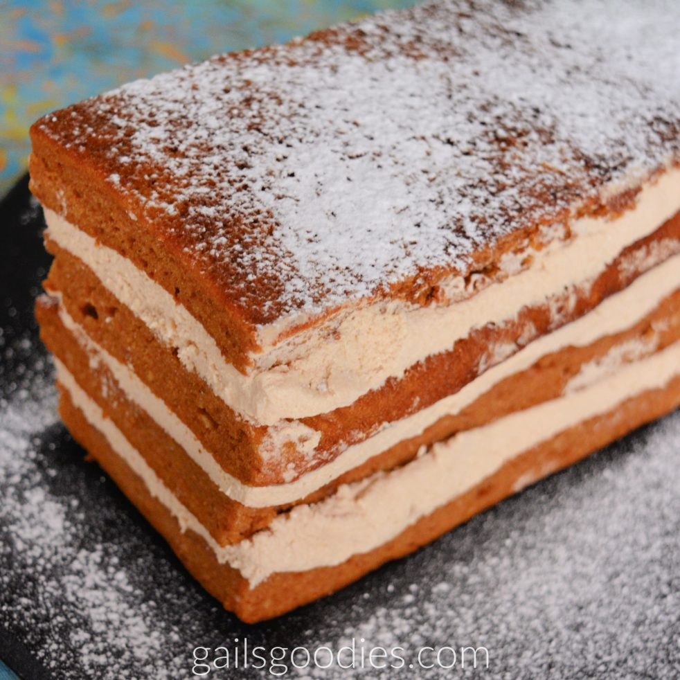 This is a view of the side and end of the pumpkin spice kahlua cream torte. There are four rectangular layers of orange pumpkin spice cake. Kahlua cream fills the space in between each layer. The top of the cak is dusted with powdered sugar.