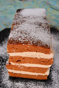 This is the end view and about 30 degrees above. There are four rectangular layers of orange pumpkin spice cake. Kahlua cream fills the space in between each layer. The top of the cak is dusted with powdered sugar.