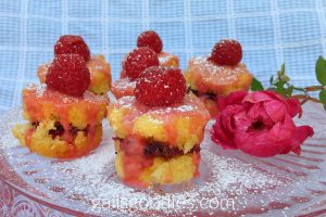 A pale rose plate with 6 rose hibiscus Victoria sponge cakes and a rose is viewed from the front and slightly above. The cakes are arranges in three columns. The column at the left of the photo has 2 cakes. The column in the middle has 3 cakes and the column on the right has 1 cake that sits at the back of the photo. The magenta rose is on the right in front of the single cake. Each cake has two layers of golden sponge cake with a layer of dark purple jam in the middle. The medium pink hibiscus glaze tops each cake and drizzles down the sides. There is also a single raspberry on each cake and each cake is dusted with powdered sugar.