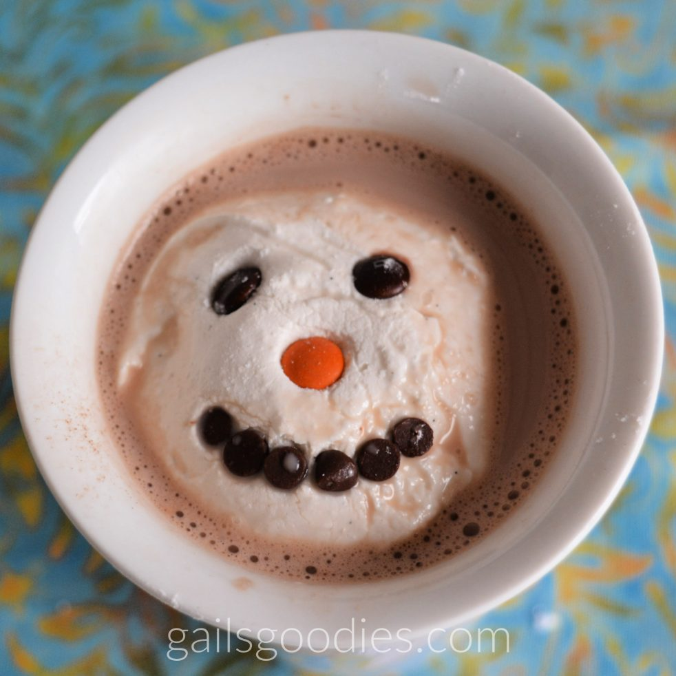 This is a view directly above a white mug filled with hot chocolate. A marshmallow topper sits in the middle of the hot chocolate and takes up most of the top of the mug. The round white marshmallow is decorated with brown mini M&M eyes, an orange mini M&M nose and six mini chocolate chips arranged in an arc to form a smiling mouth.i