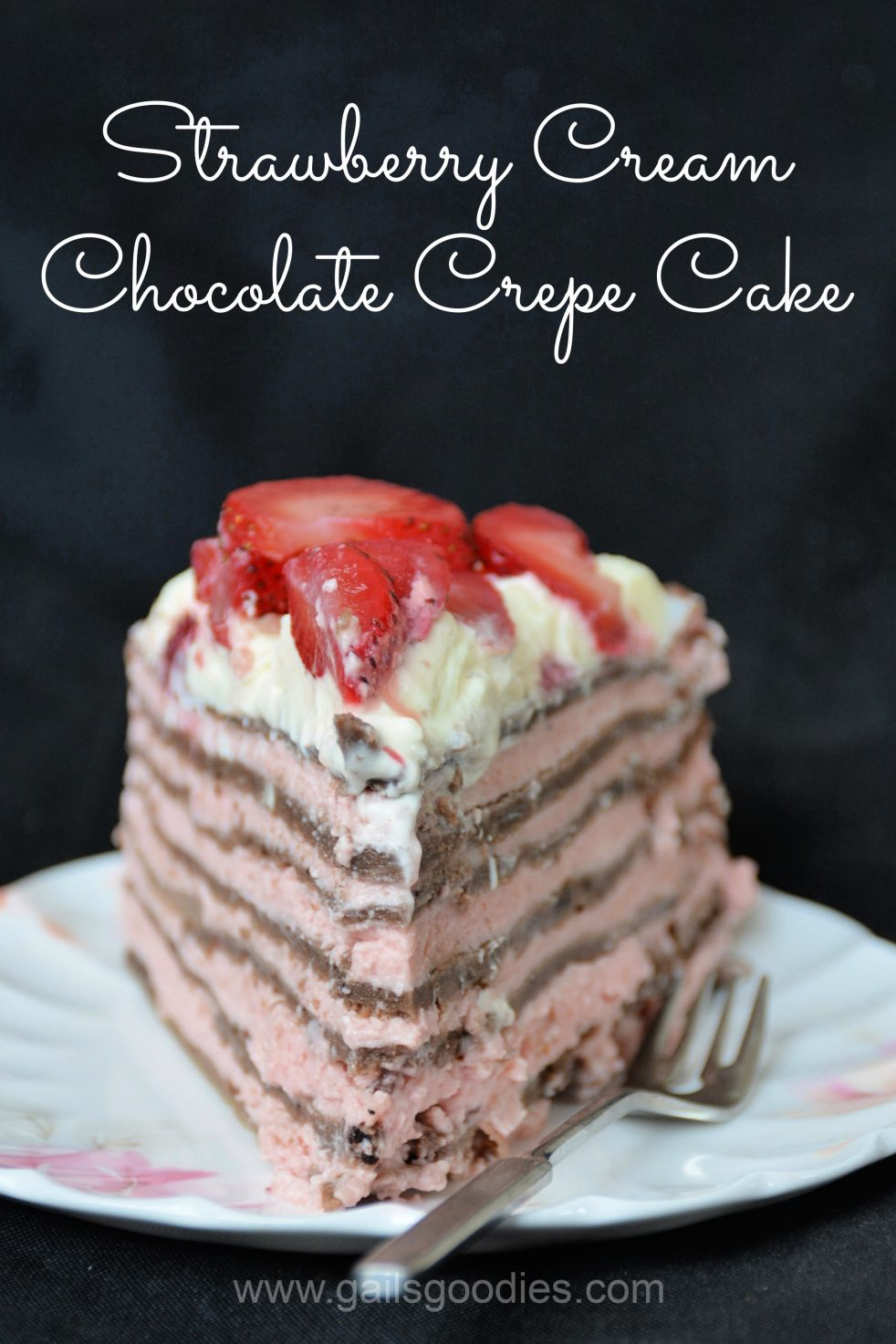 """A slice of Strawberry Cream Chocolate Crepe Cake sits on a white plate decorated with pink flowers. The cake faces forward with the point of the slice at the front of the photo. Seven milk chocolate colored crepes alternate with layers of light pink strawberry cream. The slice is topped with whipped cream and sliced strawberries. There is a fork on the plate to the right of the cake. The words """"Strawberry Cream Chocolate Crepe Cake"""" are at the top of the photo."""