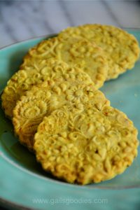 Five golden yellow turmeric shortbread cookies arc around the side of a green plate. The round cookies are embossed with flowers. The golden cookies are flecked with orange bits of turmeric tea.