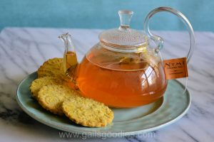 """A glass pot of light brown tea sits on a green plate. The label on the teabag says """"Numi organic tea."""" Four golden turmeric shortbread cookies curve around the edge of the plate in front of the tea pot. The golden yellow cookies are embossed with flowers.."""