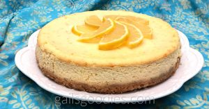 This is an oblique view of a whole goat cheese citrus cheesecake. The angle is from about 30 degrees above. The side of the cheesecake is not smooth like the top. The top is pale yellow flecked with orange spots and the side is more tan. The light brown crust is also visible at the bottom of the cheesecake. The top of the cheesecake has thinly sliced orange arranged in a circle at the center.