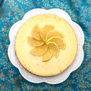 This is a top view of a whole goat cheese citrus cheesecake. Thin orange slices are arranged in a spiral flower in the middle of the cheesecake. Th cheesecake is a pale yellow with orange flecks and it sits on a white plate with scalloped edges.