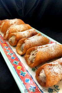 Six chocolate cherry cannolis are arrange side by side on a rectangular tray. The tray is teal and has a red-orange band around the edge. The band has alternating blue and yellow decorations. The tray is angled diagonally across the photo the the ends of the cannolis are visible as well as the sides and top. The golden brown fried shells are filld with a creamy white filling dotted with small brown and deep red flecks. The cannolis are dusted generously with powdered sugar.
