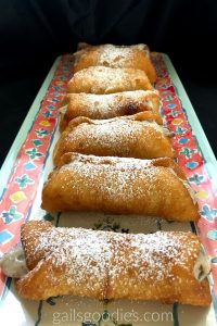 Six chocolate cherry cannolis are arrange side by side on a rectangular tray. The tray is teal and has a red-orange band around the edge. The band has alternating blue and yellow decorations. The tray is angled straight back from the cameraso only the first cannoli at the front shows the filling. The golden brown fried shells are filld with a creamy white filling dotted with small brown and deep red flecks. The cannolis are dusted generously with powdered sugar.