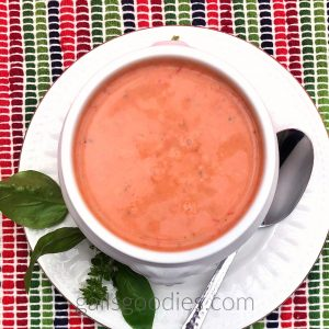 This is a top view of a white bowl filled with tomato basil soup sits on a white plate with a gold rim. There is a spoon on the plate to the right of the bowl and a sprig of basil on the plate to the left of the bowl. The tomato basil soup is a medium orange red and is speckled with dark green flecks.