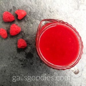 This a a view from the top of a small glass pitcher filled with Grand Marnier Raspberry Sauce. The bright red sauce stands out against the grey slate background. There are 5 raspberries scattered on the surface of the slat to the upper left of the pitcher.