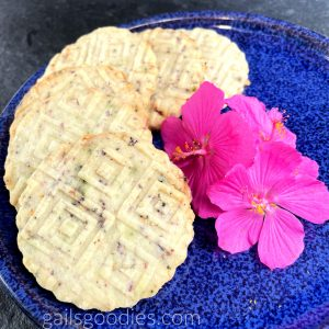 Six Hibiscus Tea Shortbread Rounds are arranged in a curve around the outside of a dark blue plate. The shortbread cookies are round and have geometric designs embossed on the top. The pale golden cookies have dark purple flecks of hibiscus tea. There are three fuchsia flowers in the middle of the photo.