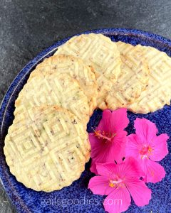 Six Hibiscus Tea Shortbread Rounds are arranged in a curve around the outside of a dark blue plate. The shortbread cookies are round and have geometric designs embossed on the top. The pale golden cookies have dark purple flecks of hibiscus tea. There are three fuscia flowers in the lower right corner of the photo.