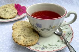 Two hibiscus tea shortbread cookies sit on the saucer to the left of a cup of tea. The golden cookies are embossed with delicate flowers and are flecked with purple specks of hibiscus tea. There is a plate of cookies out of focus in the background in the upper left corner of the photo.