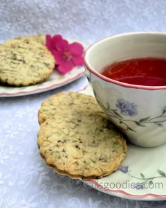 Two hibiscus tea shortbread cookies sit on the saucer of a cup of tea. The golden cookies are embossed with delicate flowers and are flecked with purple specks of hibiscus tea. The tea cup to the right of the cookies is only half visible. There is a plate of cookies out of focus in the background in the upper left corner of the photo.
