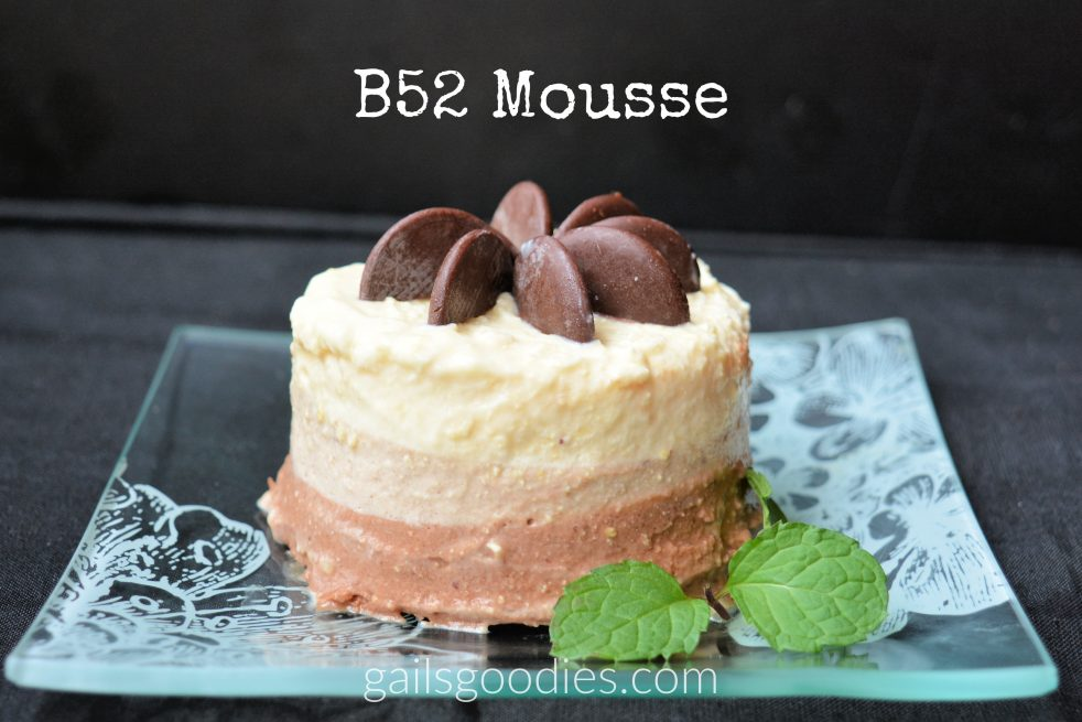 "B52 mousse sits on a glass plate etched with flowers. The mouse is shaped into a short cylindar. There are three layers in the mousse. The bottom layer is a medium brown. the middle layer is a pale brown and the top layer is alight orange. Dark chocolate discs that have been cut in half are arranged vertically on top of the mousse to make a flower. There is a sprig of mint in the lower right corner of the plate. The words ""B52 mousse"" are at the top."